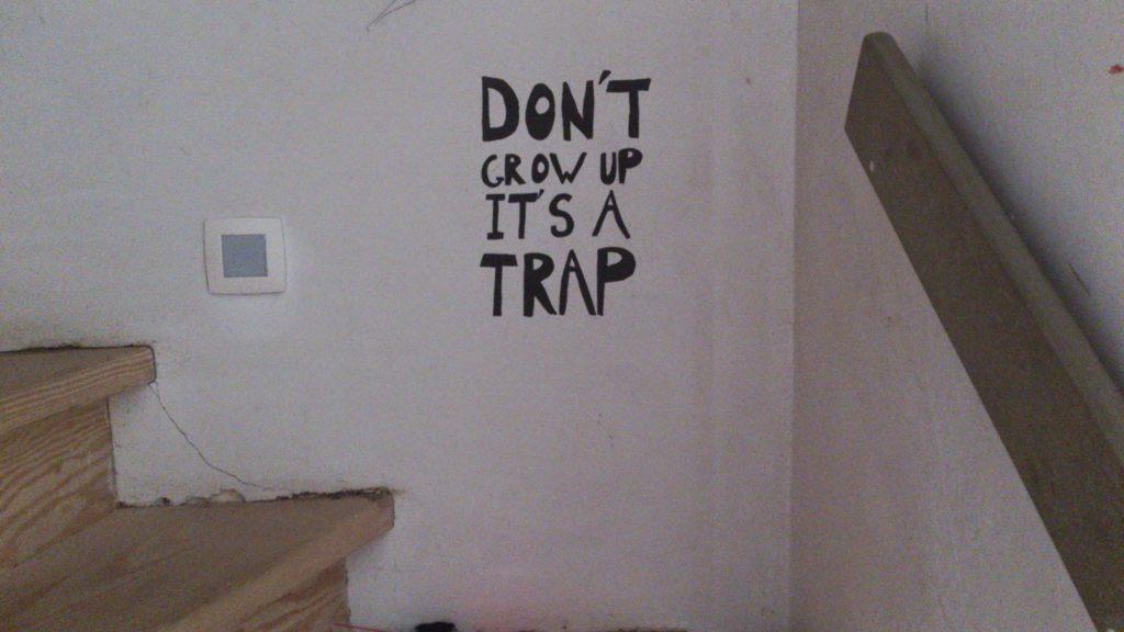 De rekst 'Don't grow up, it's a trap' staat geschilderd bovenaan een... trap.